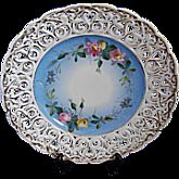 "The central design is blue and white background with a delicate pink and yellow floral design and finally surrounded by gold trimmed reticular edge. The plate measures 9"" across from edge to edge."