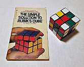 "An original Rubiks Cube from Ideal Toy with the paperback guide ""The Simple Solution to Rubik's Cube"" by James G. Nourse (1981)"