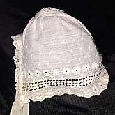 Our bonnet is fashioned from sheer cotton muslin with insets of needle-run tulle. Early 19th century muslin, which is almost transparent, is greatly superior to the heavy muslin of today.The embroidered florets are executed in chain stitchâ€&#