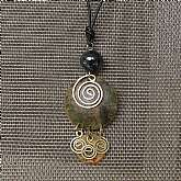 * Very earthy design that incorporates many of the elements of nature in the design -- brass spirals, patina finished copper, glass, and leather.* All elements come together to form a beautiful necklace that can be adjusted to desired length by modifyin