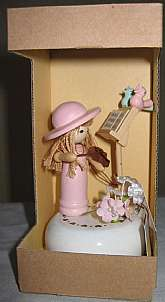 * This adorable, wooden, Lefton musical figurine is circa early 1970s. Dressed in pink, including a hat, this wooden little girl  plays her violin surrounded by silk flowers and two little, wooden birds that appear to be singing along.  The music stand ev