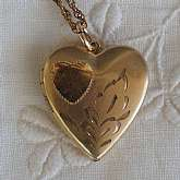 Beautiful antique Victorian engraved heart locket that measures just under an inch and is hung on an 18 inch twisted link chain.  The locket is engraved with a heart and leaves on the top.  It is the perfect classic edition for any bride on her wedding da