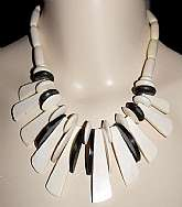 Gorgeous vintage carved ivory colored carved cow bone bead tribal necklace with elk horn contrasting beads done in a fringe style!  The necklace is comprised of 3 different handmade bone beads: round, oval tubes and finger beads.  The elk horn are disk an