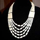 Gorgeous vintage carved ivory colored carved cow bone bead tribal necklace done in 5 amazing strands!  The necklace is comprised of 3 different handmade bone beads: round, tear drop and rectangular tubes.  There are silver tone spacers and a hook clasp.