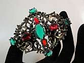 Gorgeous antique renaissance revival emerald green & red Czech glass brooch.. Set in a pot metal this brooch is from the deco era and in a renaissance revival style.. The very ornate frame is filled and layered with scroll design that is aesthetically