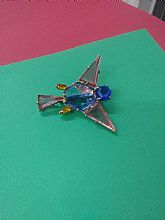 A metal bird with colored shapes to fill the metal and a blue rhinestone face