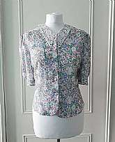 1980's vintage green, blue, pink and white floral print short sleeved slightly cropped summer blouse with lacey collar and round pearlised buttons in size 16Measurements in inches Shoulder: 34
