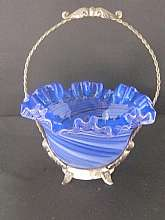 This antique Victorian Brides Basket has an almost cobalt blue fluted bowl and sits in a metal base with a handle.  The base has the finish wearing away due to age. The bowl is seven inches diameter and four inches hig