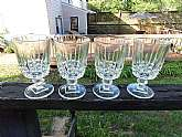 This is a set of four footed clear glass water glasses.  They're a nice heavy glass.  They stand 6 inches tall and have an opening diameter of 3 1/4 inches. They hold 8 ounces of liquid.  The glasses are in good  used condition with no chips or cracks.