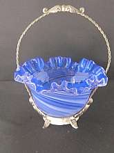 This antique Victorian Brides Basket has an almost cobalt blue fluted bowl and sits in a metal base with a handle.  The base has the finish wearing away due to age.  It's still looks good though.  The bowl is 7 by 4 inches.