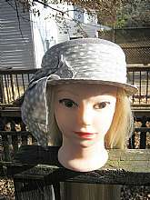 This is a nice Lucila Mendez summer hat from the 1960's.  The hat is a grey blue with a matching polka dot wide hat band.  There is a wide  embellishment on one side in the same material as the band and is finished with handmade button spirals.