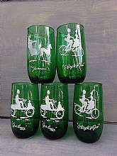 This is a set of five Anchor Hocking water glasses.  They are emerald green glass with white stenciled vintage transportation vehicles.  They are from the 1950s.  The glasses hold approximately 12 ounces.  They depict different vehicles.