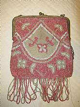 This is a sweet pink and white beaded flapper bag from the early 1900's.  It measures 5 3/4 by 5 1/4 inches, not including the fringe.  The top of the purse is metal and has a clasp closure.