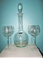This beautiful Toscany decanter with stopper and four matching stemware glasses was handblown in Romania.  It has flowers etched into the glass.  The decanter stands sixteen inches high including the stopper.   The glasses are 7 1/2 inches high.