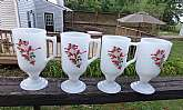 This is a set of four Christmas Irish coffee mugs.  They are milk glass with bells and holly  design.  The mugs hold 8 ounces and are footed.  They stand 5 1/2 inches tall.  The rim has a diameter of 2 1/2 inches.  The mugs are in good used condition with