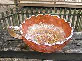 This is a beautiful marigold amber Carnival Glass Quilted Diamond Nappy Bowl with Handle. It is in very good used condition. There are no chips or cracks. The bowl measures 5 1/2 inches across and stands 2 inches high.