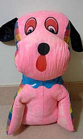 This is a 1960's stuffed dog large carnival prize.  The entire front of the dog is a bubblegum pink fabric (looks like someone may have sewn up a little hole along the front seam) and the back is a colorful checkered fabric.  The dog has a soft plastic ru
