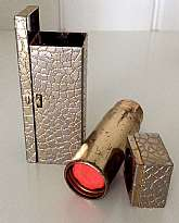 "This listing is for a stunning 1950's gold tone metal, mirrored lipstick case and coral pink lipstick.  The 2"" metal box has a little lid that pops up when the tiny button is pushed exposing a mirror.  The square lid of the box can be removed exposin"