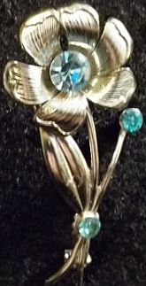 Silver metalcast flower lapel pin with blue stones