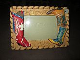 A resin picture frame with western boots all around  5 in. x 7 in. Holds a 4 in. x 5 in. picture.