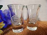 Set of 2 One-ounce shot glasses. Clear glass with white heat bonded transfer reading