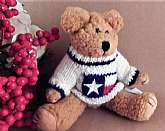 Adorable beige stuffed plush bear by Berkeley Designs. Nubbly beige jointed stuffed plush bear wearing a red, white and blue stars and stripes knitted sweater.