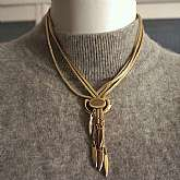 Exceptional vintage serpentine or snake chain fringe or tassel necklace by Monet.  It is gold tone and has three slinkly snakelike chains on each side  that come together with an adjustable slide so that you can shorten or lengthen the tassels.  The neckl