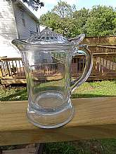 This is a very unusual syrup or cream pitcher.  It is heavy glass and stands 5 3/4 inches tall.  The base is 4 inches in diameter.  There are some bubbles in the glass.  The top is removable but fits so that it can be  opened with the thumb safely.