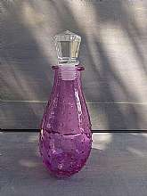This is a nice purple or amethyst hobnail bottle with a glass stopper.  The stopper is part plastic and part faceted glass.  The bottle has a wide body and narrows at the opening.  There is a  #8 on the bottom. The bottle is 7 inches tall with stopper