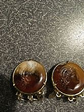 Vintage Onyx Clip Earrings. Round brown and white onyx set on gold metal backing with three dangling coins on bottom.