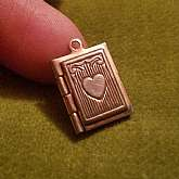 "This is a sweet little book locket/charm for charm bracelets.It is sterling silver.It dates to the 1940'sIt has hinges at the side and opens to put two tiny photos.Engraved heart on the front.5/8"" long.This would have been worn on a charm brace"